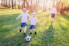 garçons jouant le football en parc Photo stock