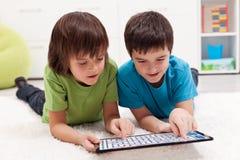 Garçons jouant le jeu de labyrinthe sur l'ordinateur de tablette Photographie stock libre de droits