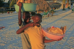 Garçons locaux vendant le pain à la plage de Boca Chica photos stock