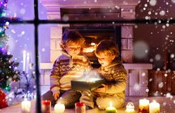 Garçons mignons d'enfant en bas âge, jumeaux blonds jouant ensemble et boîte-cadeau s'ouvrant de surprise sur Noël Photos libres de droits