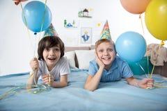 Garçons mineurs joyeux dans des chapeaux drôles de cône Photographie stock libre de droits