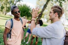Garçons multi-ethniques donnant la haute cinq tout en se réunissant en parc Photos stock