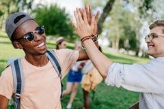 Garçons multi-ethniques donnant la haute cinq tout en se réunissant en parc Image libre de droits