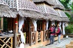 Garçons que cantam em casas da casa de campo das folhas do bambu e do coco fotografia de stock royalty free
