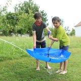 Garçons remplissant parapluie avec de l'eau Photographie stock