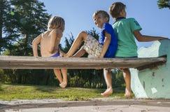 Garçons s'asseyant sur le banc en parc Photographie stock
