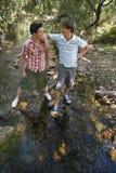 Garçons se tenant prêt le courant dans la forêt Photo stock