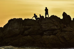 Garçons sur le coucher du soleil de lumière de roche Images libres de droits