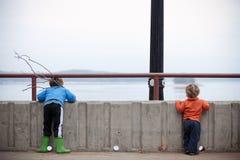 Garçons wating le lac avec des bâtons Image libre de droits