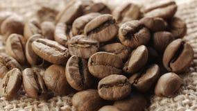 Garść brąz, piec kawowe fasole na burlap grabije tło, zakończenie up, obracanie zbiory