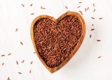 garść surowi czerwoni ryż w drewnianym pucharze w formie serca na bielu dryluje tło obraz royalty free