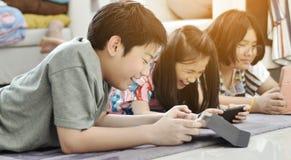 Gar?on asiatique et fille jouant le jeu au t?l?phone portable ainsi que le visage de sourire photographie stock