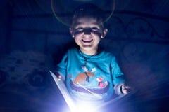 Gar?on caucasien d'amusement lisant un livre la nuit avec la lampe-torche dans la main ? la maison Fond noir images libres de droits