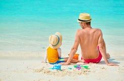 Gar?on d'enfant en bas ?ge sur la plage avec le p?re photographie stock libre de droits