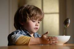 Gar?on d'enfant mangeant de la nourriture saine ? la maison Bonjour dans la famille heureuse Peu gar?on s'asseyant ? la table et  image stock