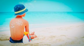 Gar?on de protection de Sun petit avec le suncream ? la plage photo libre de droits