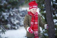 Gar?on dr?le de petit enfant dans des v?tements color?s jouant dehors pendant les chutes de neige Loisirs actifs avec des enfants photos libres de droits