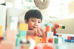 Gar?on empilant des blocs de jouet sur un salon pour le jouet ?ducatif photos stock