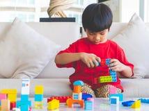 Gar?on empilant des blocs de jouet sur une table de salon photos libres de droits