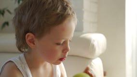 gar?on 6 an mangeant la pomme verte et essayer de retirer des dents de lait clips vidéos