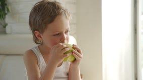 gar?on 6 an mangeant la pomme verte et essayer de retirer des dents de lait banque de vidéos