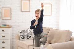 Gar?on mignon avec le microphone sur le sofa dans la chambre image libre de droits