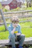 Gar?on s'asseyant sur le banc avec le bouquet des fleurs s?lectionn?es fra?ches photo stock