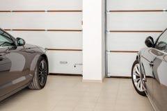 Garage à la maison pour deux véhicules intérieurs Nettoyez les voitures de luxe garées à la maison Portes à télécommande automati Photos stock
