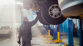 Garage automobile service - a mechanic checks the transmission. Wide angle royalty free stock images