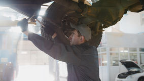 Garage automobile service - a mechanic checks the wheel, close up Stock Images