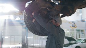 Garage automobile service - a mechanic under bottom of car checks the wheel, close up. Close up, horizontal stock footage