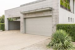 Garage in big house. Big grey house with a drive way and a parking garage Stock Image