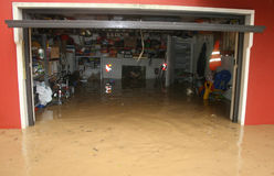 Garage with bike and boxes during a flood and the brown river fl Stock Image