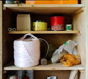 Garage cabinet with clutter. A wooden cabinet in a garage containing rope, tools, boxes, cans and other clutter royalty free stock photos