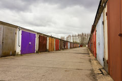 Garage community perspective on a cloudy day. With purple red brown doors stock photos