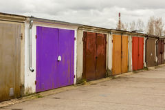 Garage community perspective on a cloudy day. With purple red brown doors stock photo