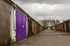 Garage community perspective on a cloudy day. With purple red brown doors stock images