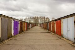 Garage community perspective on a cloudy day. With purple red brown doors royalty free stock images