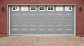 Garage con la calzada de las puertas, de la pared de ladrillo y del asfalto fotos de archivo