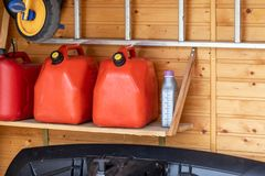 Garage corner with three red plastic fuel cans , staircase and snow plough for atv with wooden wall on background. Petrol gas. Containers reserves storage at royalty free stock photography