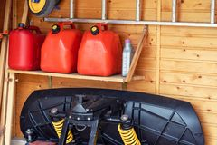 Garage corner with three red plastic fuel cans , staircase and snow plough for atv with wooden wall on background. Petrol gas. Containers reserves storage at royalty free stock photos