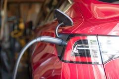Garage dedans branché par véhicule électrique rouge photographie stock libre de droits