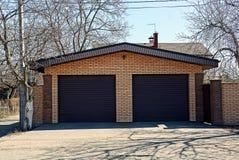 Garage del mattone con due portoni marroni Immagine Stock