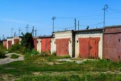 Garage del mattone con i portoni rossi del metallo della cooperativa del garage Fotografie Stock Libere da Diritti