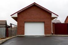 Garage del mattone rosso con i portoni Fotografia Stock