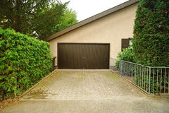 Private garage for vehicles from the house. Private garage near the house with automatic doors and paved alley in front of it stock photo
