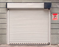 Garage door with no parking sign. Hanging on the wall royalty free stock photo