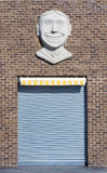 Garage door at a old brick wall building, smiling face Royalty Free Stock Photos