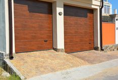 Garage door for two cars with pathway pavement and plastic gutter pipes. Replacing and Repair Garage Door Panels Royalty Free Stock Photo