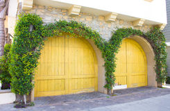 Garage Doors. Lovely wooden garage doors, covered in ivy, on a stone house Stock Photo